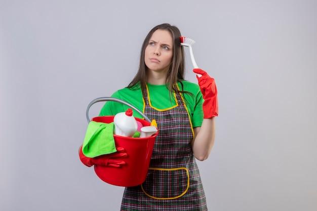 Guardando il pensiero laterale pulizia giovane donna che indossa l'uniforme in guanti rossi che tengono gli strumenti di pulizia graffia la testa con la spazzola di pulizia sulla parete bianca isolata