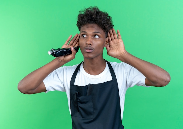 Looking at side thinking young afro-american male barber wearing uniform holding hair clippers and showing listen gesture isolated on green wall