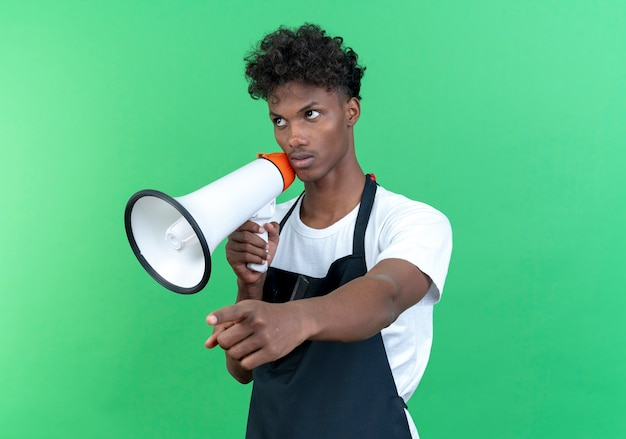 Looking at side thinking young afro-american male barber wearing uniform holding loudspeaker and points at side isolated on green background
