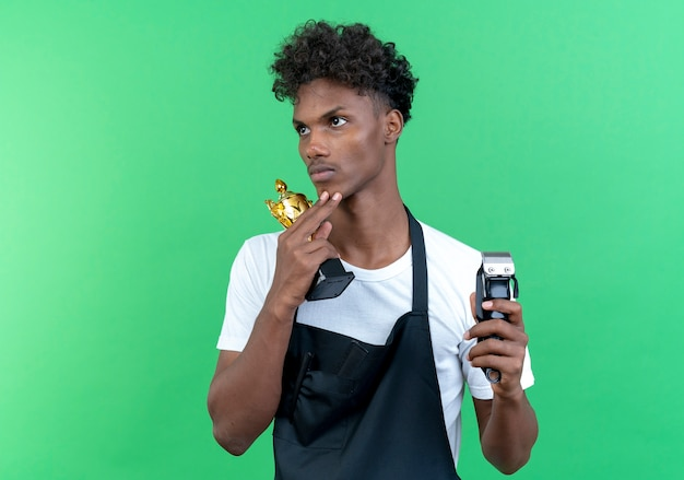 Looking at side thinking young afro-american male barber wearing uniform holding winner cup with hair clippers isolated on green background
