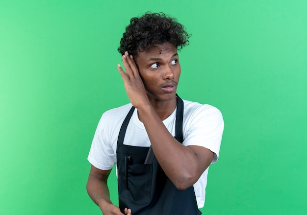 Looking at side thinking young afro-american male barber wearing uniform showing listen gesture isolated on green background