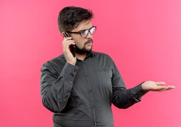 Guardando il pensiero laterale giovane imprenditore con gli occhiali parla sul telefono e tendendo la mano a lato isolato sulla parete rosa