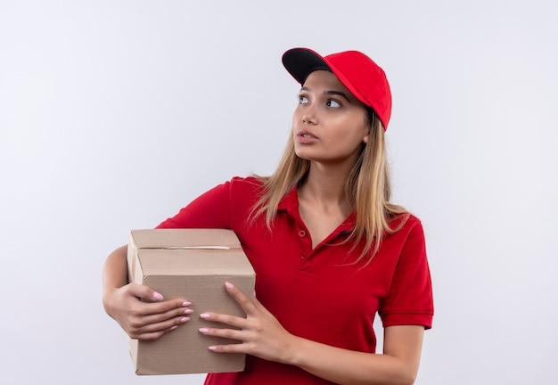 Guardando il pensiero laterale giovane ragazza di consegna che indossa l'uniforme rossa e la scatola di contenimento del cappuccio isolata sulla parete bianca