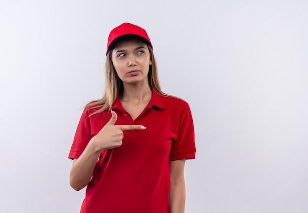 Guardando il pensiero laterale giovane ragazza delle consegne che indossa uniformi rosse e punti di protezione sul lato isolato sulla parete bianca con lo spazio della copia