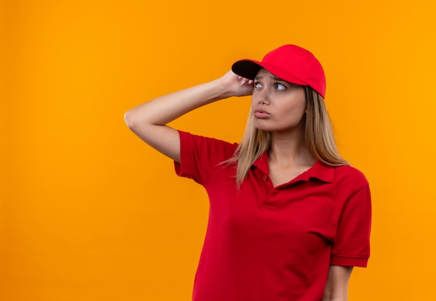 Guardando il pensiero laterale giovane donna di consegna che indossa l'uniforme rossa e il cappuccio mettendo la mano sulla testa