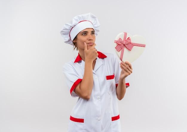 Guardando il lato pensando giovane femmina cuoco indossando lo chef uniforme tenendo la scatola a forma di cuore mettendo la mano sul mento sul muro bianco isolato con lo spazio della copia