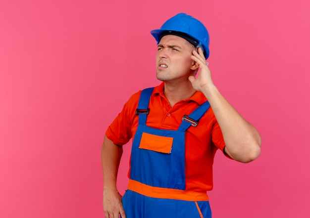 Looking at side thinking young male builder wearing uniform and safety helmet putting hand on ear