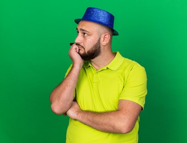 녹색 벽에 고립 된 파티 휘파람을 들고 파란색 파티 모자를 쓰고 측면 생각 젊은 남자를 찾고