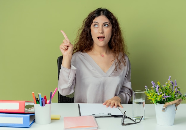 Looking at side thinking young pretty female office worker sitting at desk with office tools points at side isolated on olive background with copy space