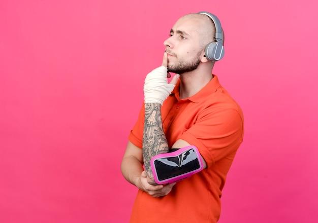 Guardando il lato pensando giovane uomo sportivo con fasciatura da polso che indossa le cuffie con fascia da braccio del telefono e mettendo la mano sul mento isolato sul muro rosa