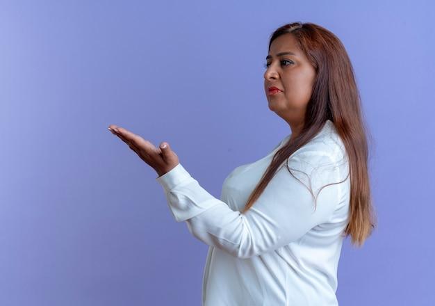 Guardando i punti di donna di mezza età caucasici casuali sgradevoli di lato con la mano a lato