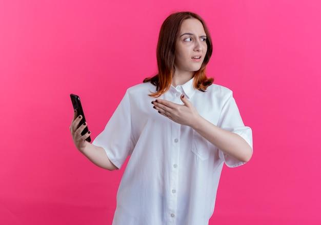 Guardando il lato imbarazzato giovane ragazza redhead holding e punti con la mano al telefono isolato su sfondo rosa