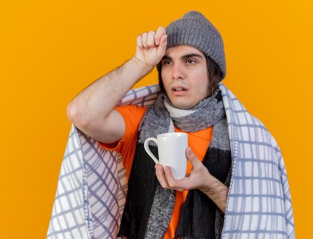 Guardando il lato debole giovane uomo malato che indossa un cappello invernale con sciarpa avvolta in un plaid che tiene tazza di tè mettendo la mano sulla fronte isolato su sfondo arancione