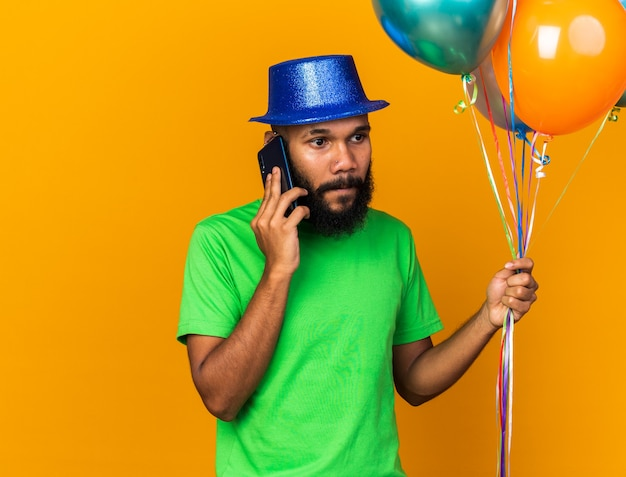 Looking side young afro-american guy wearing party hat holding balloons speaks on phone