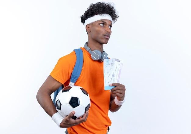 Guardando il lato giovane afro-americano sportivo uomo che indossa la fascia e il braccialetto tenendo palla e biglietti isolati su sfondo bianco