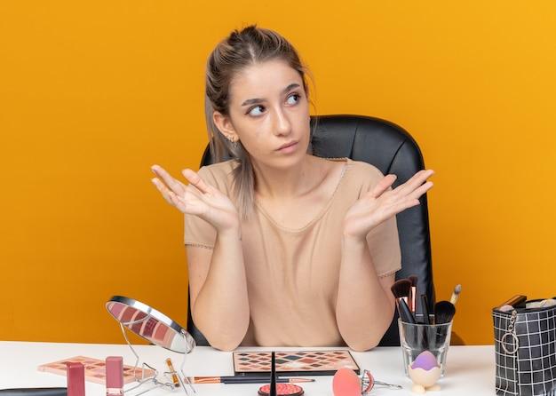 Молодая красивая девушка сидит за столом с инструментами для макияжа, разводя руками, изолированными на оранжевой стене