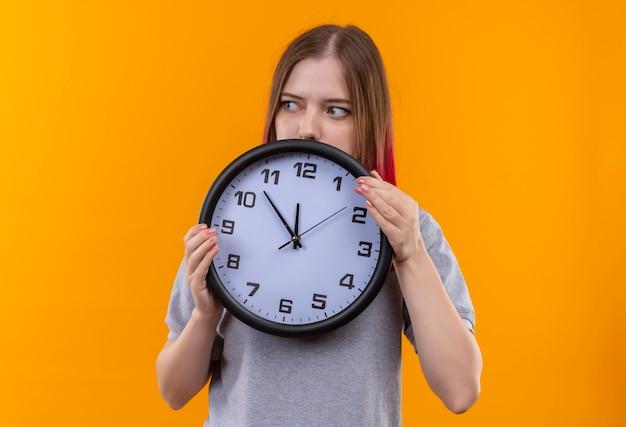 Guardando lato giovane bella ragazza che indossa t-shirt grigia tenendo l'orologio da parete isolato su sfondo giallo Foto Gratuite