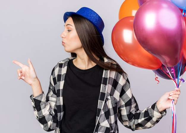 Looking at side young beautiful girl wearing party hat holding balloons points at side