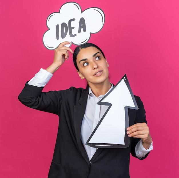 頭にアイデアバブルを置く方向マークを保持している黒いブレザーを身に着けている側を見て若い美しい女性
