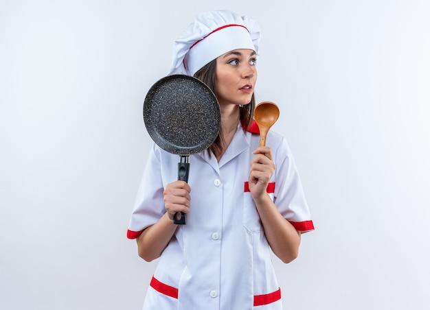 Guardando lato giovane cuoca che indossa l'uniforme dello chef tenendo la padella con il cucchiaio isolato sul muro bianco