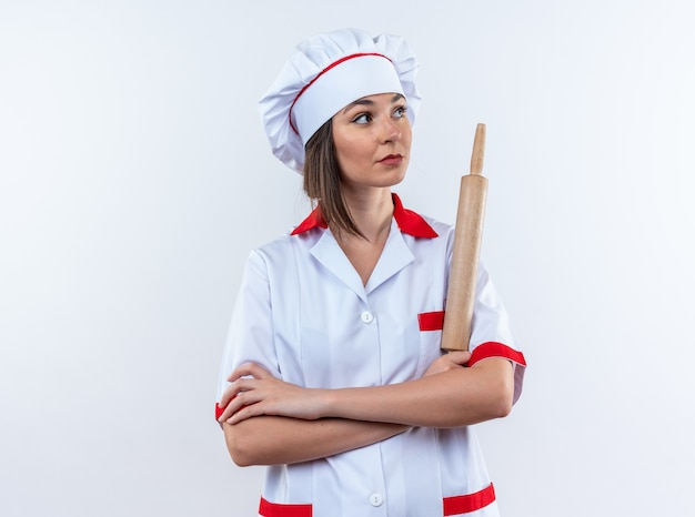 白い壁に分離された手を横切って麺棒を保持しているシェフの制服を着た側の若い女性料理人を見て
