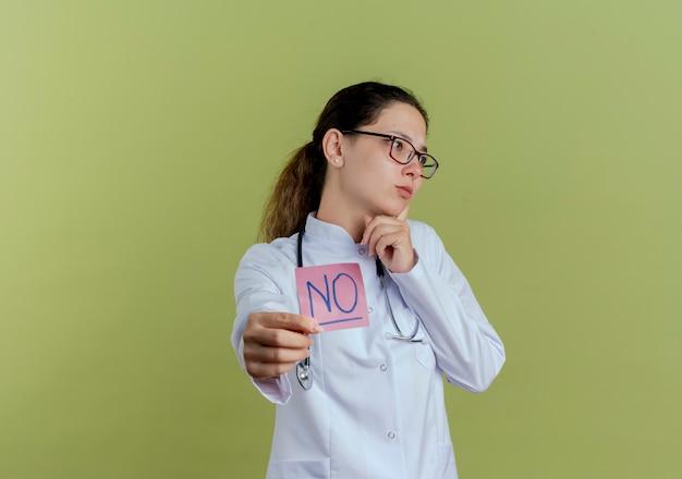 Guardando lato giovane medico femminile che indossa abito medico e stetoscopio con gli occhiali tenendo fuori carta nota isolata