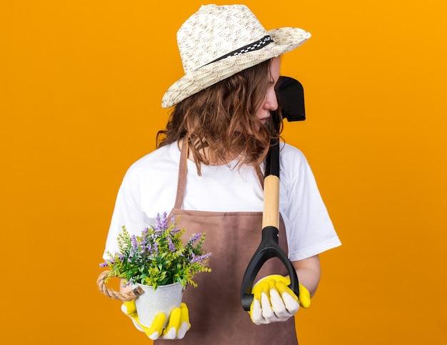 Guardando lato giovane giardiniere femminile che indossa cappello da giardinaggio tenendo il fiore in vaso di fiori con vanga isolato su parete arancione
