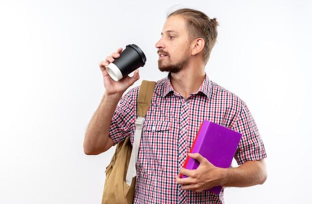 Глядя стороне молодой парень студент носить рюкзак, держа книги с чашкой кофе