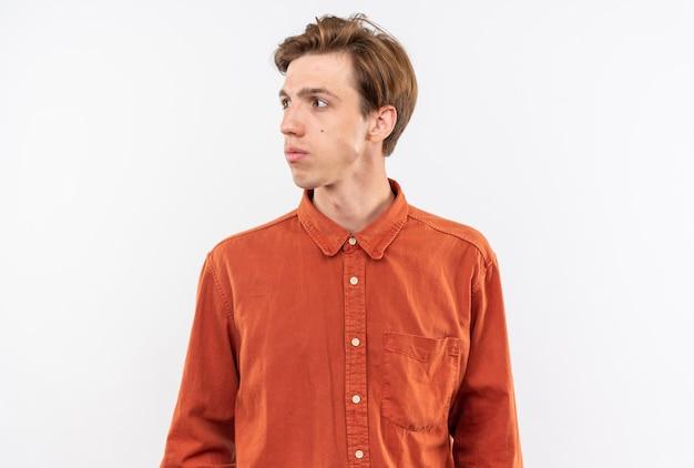 Guardando il lato giovane bel ragazzo che indossa una camicia rossa