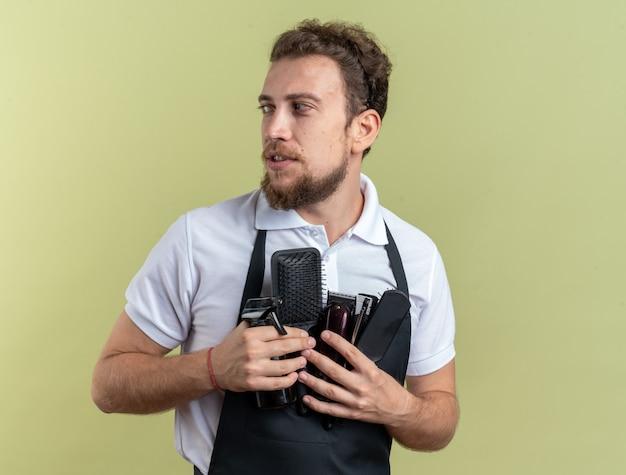 Guardando il lato giovane barbiere maschio che indossa l'uniforme che tiene gli strumenti del barbiere isolati sulla parete verde oliva
