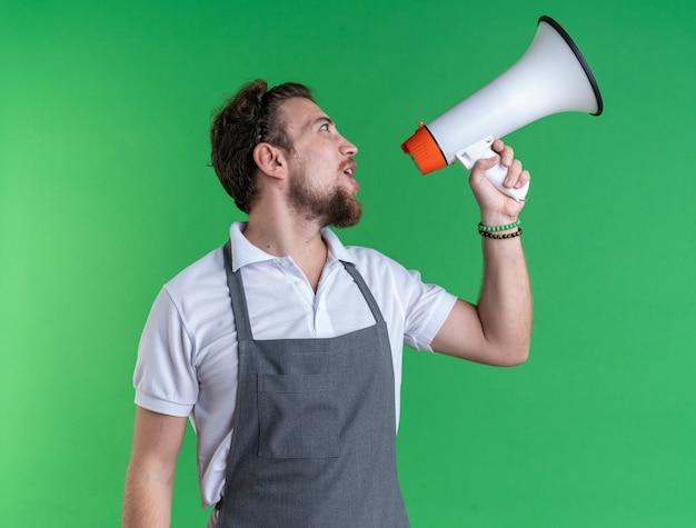 녹색 벽에 고립 된 스피커에서 말하는 유니폼을 입고 측면 젊은 남성 이발사를 찾고