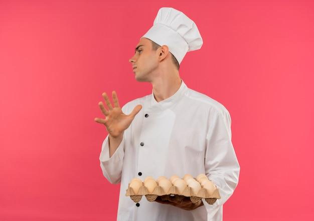 Guardando il lato giovane cuoco maschio che indossa l'uniforme del cuoco unico che tiene lotto di uova che mostrano il gesto di arresto sulla parete rosa isolata