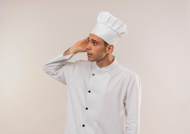 Guardando il lato giovane cuoco maschio che indossa l'uniforme del cuoco unico mettendo la mano sull'orecchio sulla parete bianca isolata