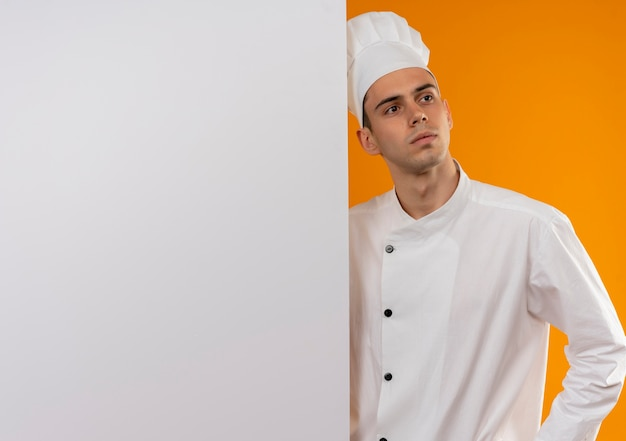 Looking at side young male cool wearing chef uniform holding white wall on isolated yellow wall with copy space