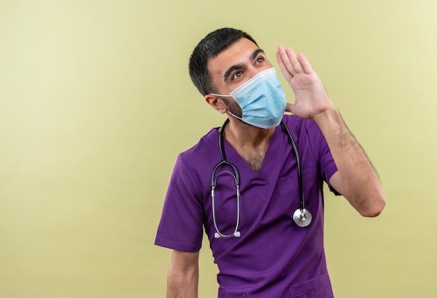 Guardando il lato giovane medico maschio che indossa abiti chirurgo viola e maschera medica stetoscopio chiamando qualcuno su sfondo verde isolato