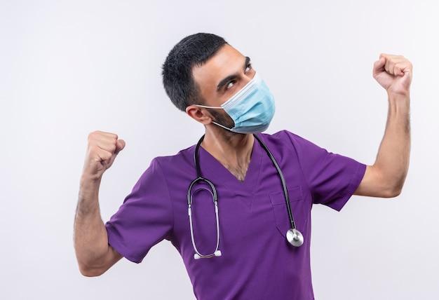 Guardando lato giovane medico maschio che indossa abiti chirurgo viola e maschera medica stetoscopio facendo un gesto forte su sfondo bianco isolato