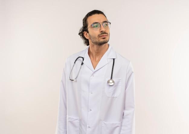 Guardando lato giovane medico maschio con occhiali ottici che indossa una veste bianca con lo stetoscopio