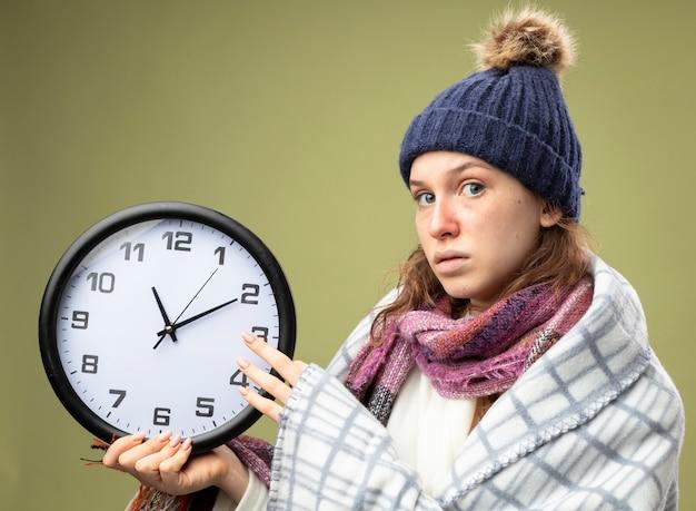 Глядя прямо перед собой молодая больная девушка в белом халате и зимней шапке с шарфом, держащая настенные часы, изолированные на оливково-зеленом