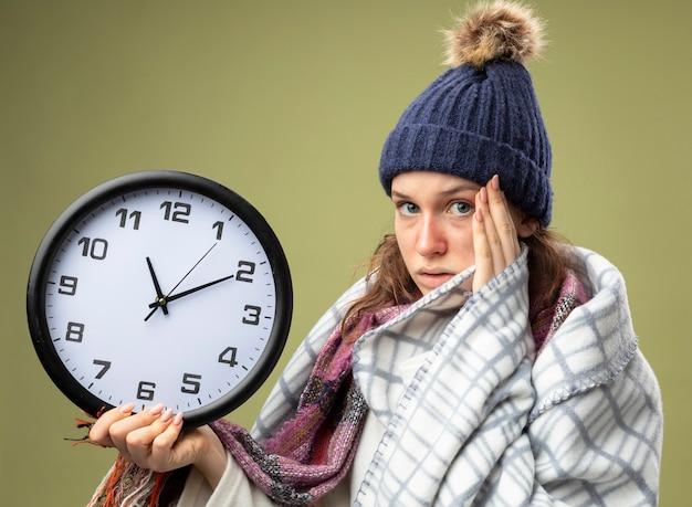Глядя прямо перед собой молодая больная девушка в белом халате и зимней шапке с шарфом держит настенные часы, завернутые в плед, положив руку на храм, изолированный на оливково-зеленом