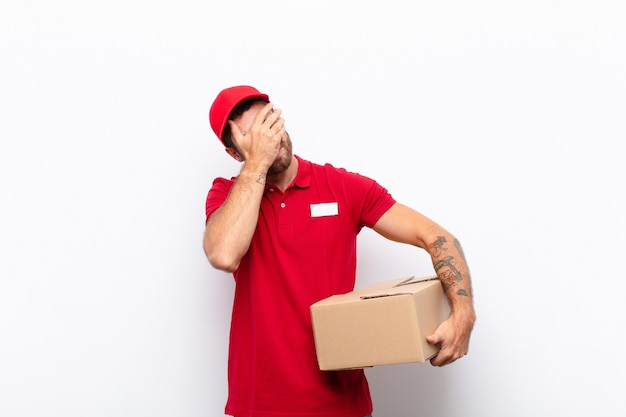 Looking stressed, ashamed or upset, with a headache, covering face with hand. delivery concept