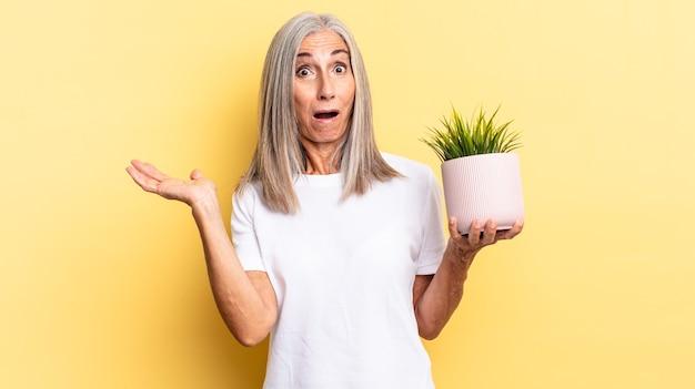 観賞用植物を持っている側に開いた手でオブジェクトを持って顎を落とし、驚いてショックを受けたように見えます