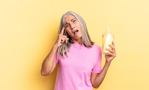 Выглядит удивленным, с открытым ртом, шокированным, осознает новую мысль, идею или концепцию и держит молочный коктейль