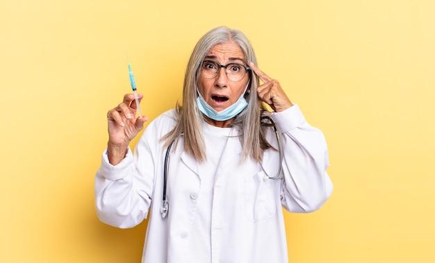 Выглядит удивленным, с открытым ртом, шокированным, осознающим новую мысль, идею или концепцию. концепция врача и вакцины