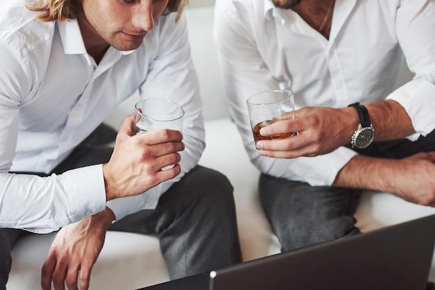 ものを探しています。ノートパソコンの近くに座ってウイスキーグラスを持っている2人のビジネスマンの粒子ビュー。