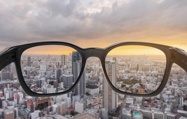 Глядя через очки на город закат, сосредоточены на объектив с размытым фоном
