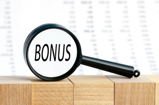 Looking through a magnifying glass at the word bonus, a business concept
