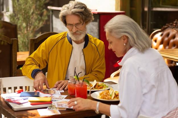 사진을 통해 찾고 있습니다. 집중된 남편과 아내가 카페 테이블에 앉아 식사를 하고 인쇄된 사진을 보고 있습니다.