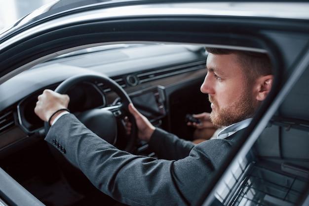 Глядя в открывшееся окно. прекрасная успешная пара пробует новую машину в автомобильном салоне.