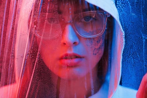 Просматривая влажный материал. студия снята в темной студии с неоновым светом. портрет молодой девушки.
