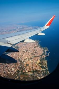 晴天時のイスタンブール上空の翼の土地での飛行中に窓の航空機を通して見る